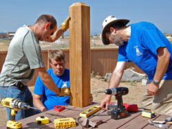Phil and Daniel help a foster parent install a deck railing on his home